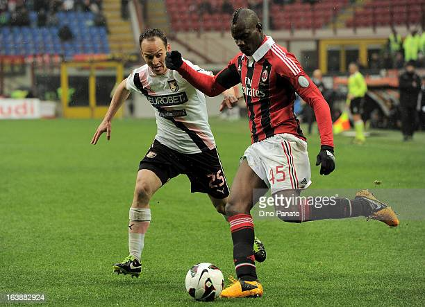 Mario Balotelli of AC Milan competes with Steve Von Bergen of US Citta di Palermo during the Serie A match between AC Milan and US Citta di Palermo...