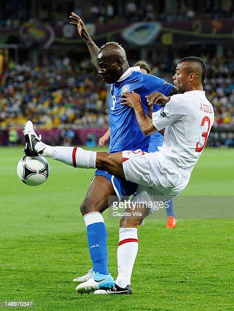 Mario Balotelli of Italy and Ashley Cole of England challenge forthe ball during the UEFA EURO 2012 quarter final match between England and Italy at...