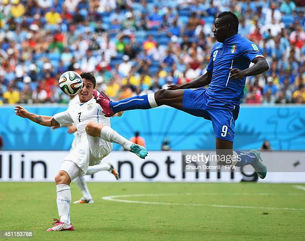 Mario Balotelli of Italy and Cristian Rodriguez of Uruguay compete for the ball during the 2014 FIFA World Cup Brazil Group D match between Italy and...