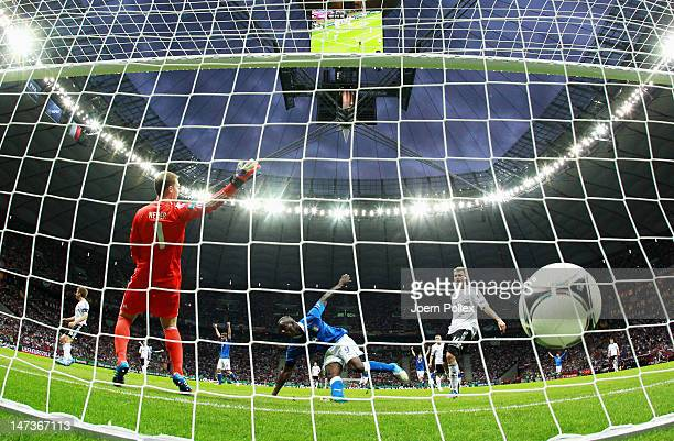 Mario Balotelli of Italy celebrates next to Holger Badstuber of Germany after scoring the opening goal past Manuel Neuer of Germany during the UEFA...