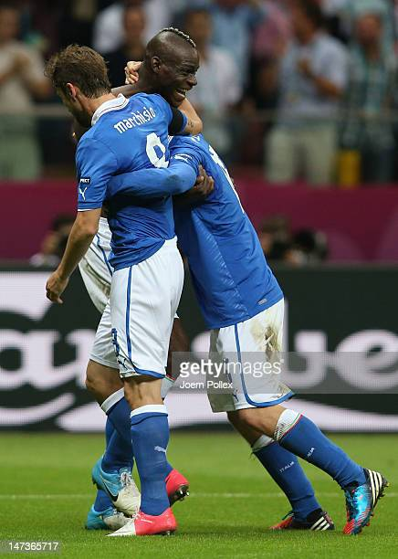 Mario Balotelli of Italy celebrates with teammates Claudio Marchisio and Daniele De Rossi after scoring his team's second goal during the UEFA EURO...