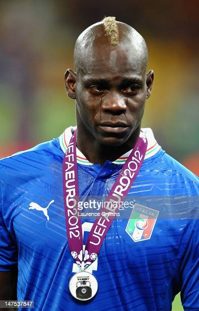 Mario Balotelli of Italy cries as he shows his dejection following defeat in the UEFA EURO 2012 final match between Spain and Italy at the Olympic...