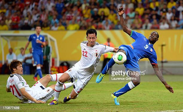 Mario Balotelli of Italy is challenged by Maya Yoshida of Japan during the FIFA Confederations Cup Brazil 2013 Group A match between Italy and Japan...