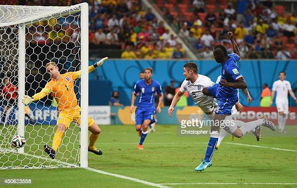 Mario Balotelli of Italy scores his team's second goal on a header past Gary Cahill and goalkeeper Joe Hart of England during the 2014 FIFA World Cup...