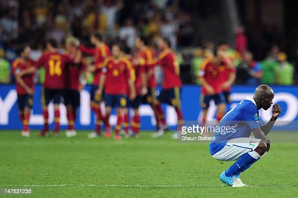 Mario Balotelli of Italy shows his dejection as the the Spanish team celebrate after Juan Mata of Spain scored their fourth goal during the UEFA EURO...