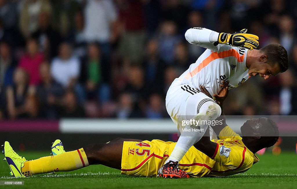 Mario Balotelli of Liverpool and Adrian of West Ham clash following a heavy tackle by Balotelli on Adrian during the Barclays Premier League match between West Ham United and Liverpool at Boleyn Ground on September 20, 2014 in London, England.