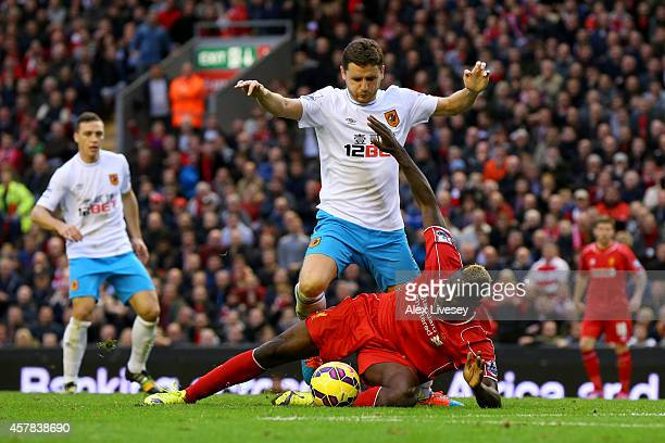 Mario Balotelli of Liverpool battles for the ball with Alex Bruce of Hull City during the Barclays Premier League match between Liverpool and Hull...