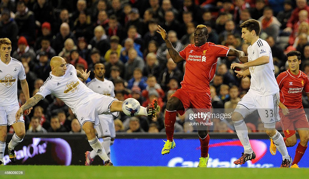 Mario Balotelli of Liverpool competes with Jonjo Shelvey of Swansea City during the Capital One Cup Fourth Round match between Liverpool and Swansea City at Anfield on October 28, 2014 in Liverpool, England.