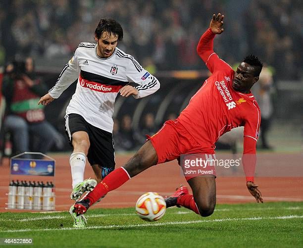 Mario Balotelli of Liverpool competes with Veli Kavlak of Besiktas JK during the UEFA Europa League Round of 32 match between Besiktas JK and...