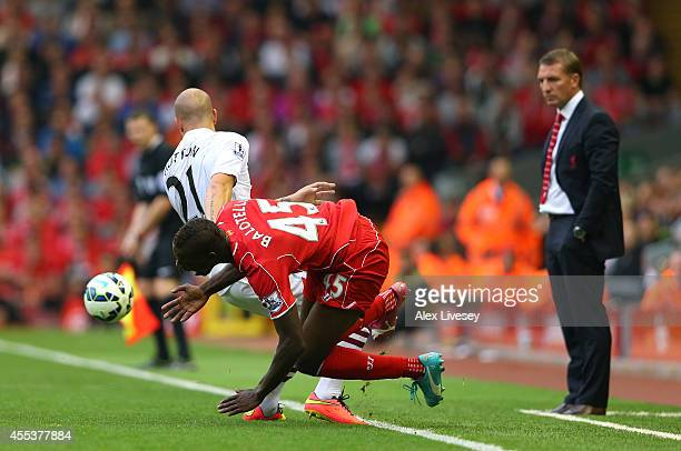 Mario Balotelli of Liverpool falls after a heavy challenge from Alan Hutton of Aston Villa as Brendan Rodgers looks on during the Barclays Premier...