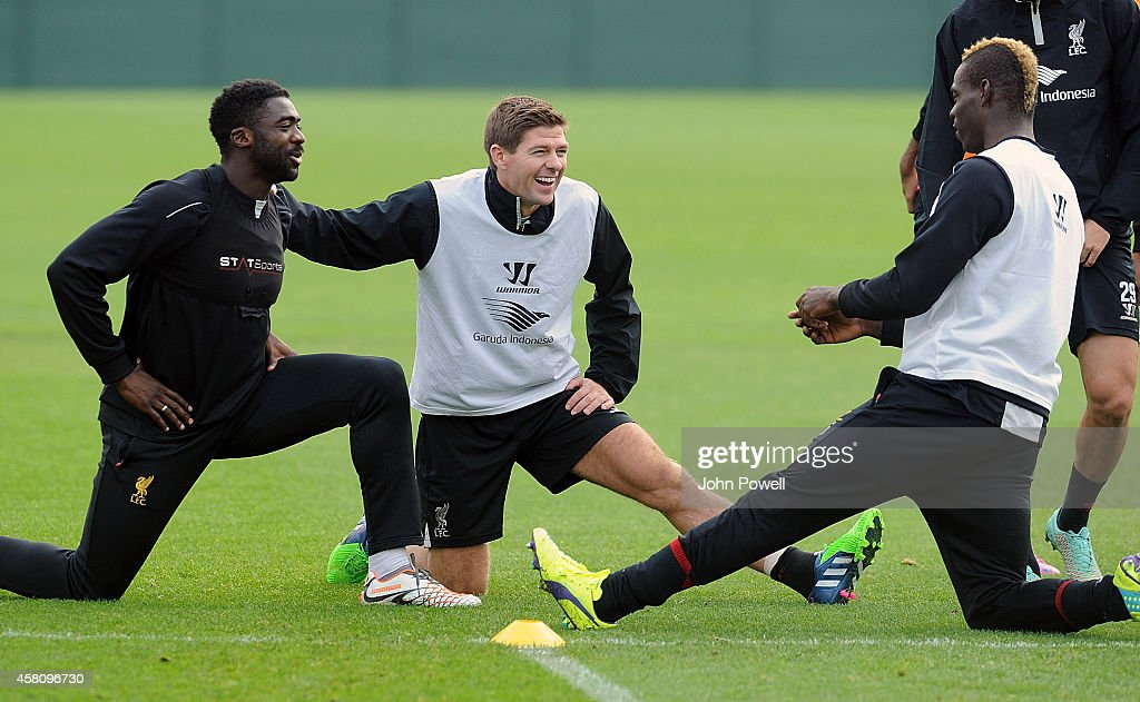 Mario Balotelli of Liverpool talks with Steven Gerrard and Kolo Toure during a training session at Melwood Training Ground on October 30, 2014 in Liverpool, England.