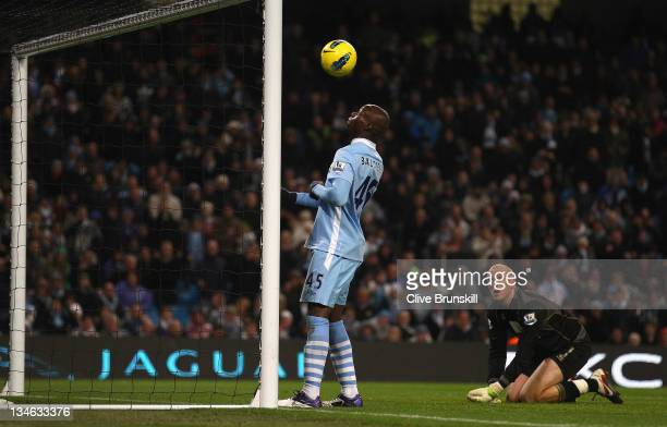Mario Balotelli of Manchester City about to score the fourth goal as Norwich City keeper John Ruddy watches during the Barclays Premier League match...