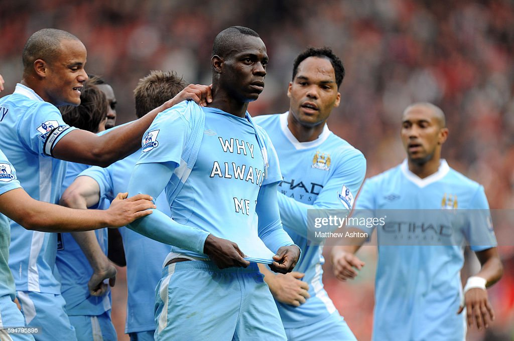 Mario Balotelli of Manchester City celebrates after scoring a goal to make it 0-1 Showing off a shirt saying 'Why Always Me?'
