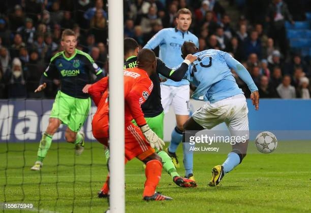 Mario Balotelli of Manchester City has his shirt pulled by Ricardo van Rhijn of Ajax in the penalty box during the UEFA Champions League Group D...