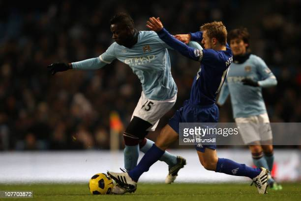Mario Balotelli of Manchester City holds off a challenge from Phil Neville of Everton during the Barclays Premier League match between Manchester...
