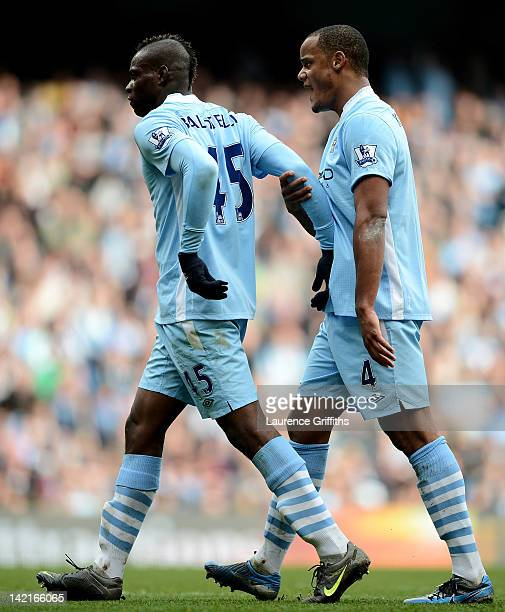 Mario Balotelli of Manchester City is restrained by team mate Vincent Kompany during the Barclays Premier League match between Manchester City and...