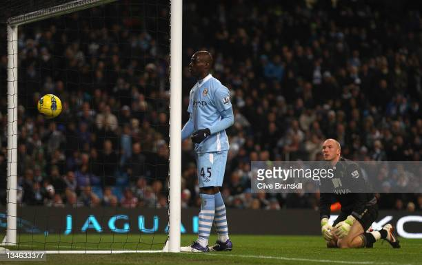 Mario Balotelli of Manchester City scores the fourth goal as Norwich City keeper John Ruddy watches during the Barclays Premier League match between...