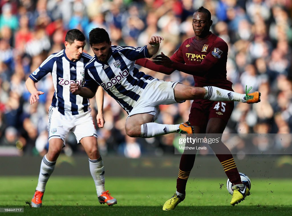 Mario Balotelli of Manchester City tackles Shane Long of West Bromwich Albion during the Barclays Premier League match between West Bromwich Albion and Manchester City at The Hawthorns on October 20, 2012 in West Bromwich, England.