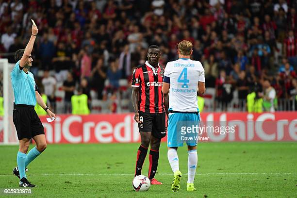 Mario Balotelli of Nice receives a yellow card for a foul on Benedikt Howedes of Schalke 04 during the Europa League match between Nice and Schalke...