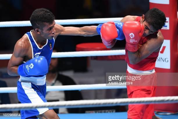 Mario Blasius Kali of Indonesia punches Sri Lanka's Thiwanka Sandaruwan Ranasinghe Palleha Muturanwellige during the men's light fly 49kg round of 32...