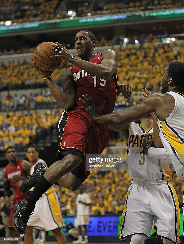 Mario Chalmers #15 of the Miami Heat leaps to pass as George Hill #3 and Ray Hibbert #55 of the Indiana Pacers defend in Game Three of the Eastern Conference Semifinals in the 2012 NBA Playoffs at Bankers Life Fieldhouse on May 17, 2012 in Indianapolis, Indiana.