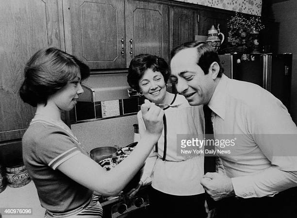 Mario Cuomo tastes cooking of daughter Margaret as Mrs Cuomo looks on