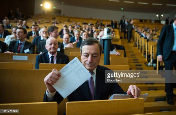 Mario Draghi president of the European Central Bank holds a document while sitting in the audience before addressing the 'ECB and its Watchers'...