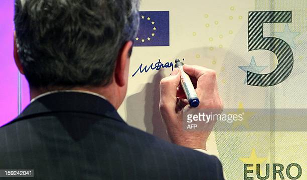 Mario Draghi President of the European Central Bank is signing a giant five euro note during the unveiling ceremony of the new 5 euros s Banknote in...