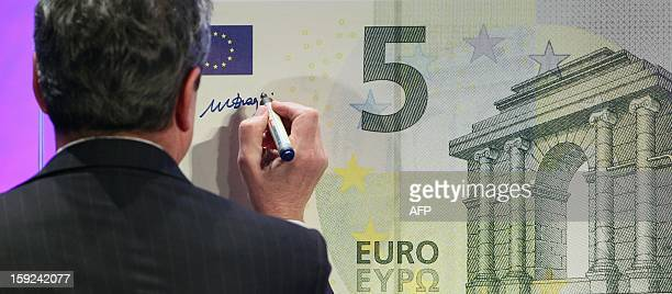 Mario Draghi President of the European Central Bank is signing a giant five euro note during the unveiling ceremony of the new 5 euross banknote in...