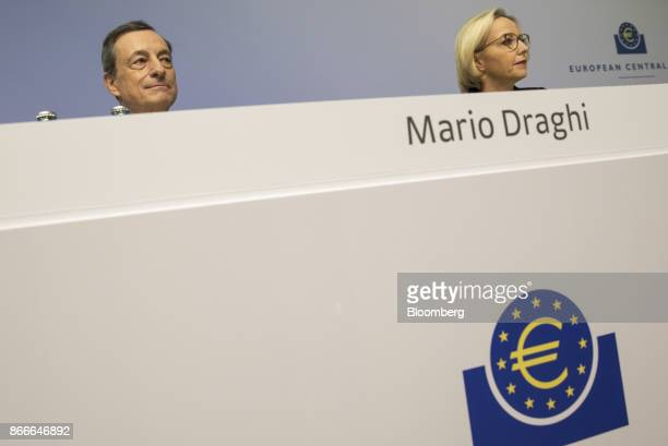 Mario Draghi president of the European Central Bank left looks on as he sits beside Christine Graeff director general for communications at the...