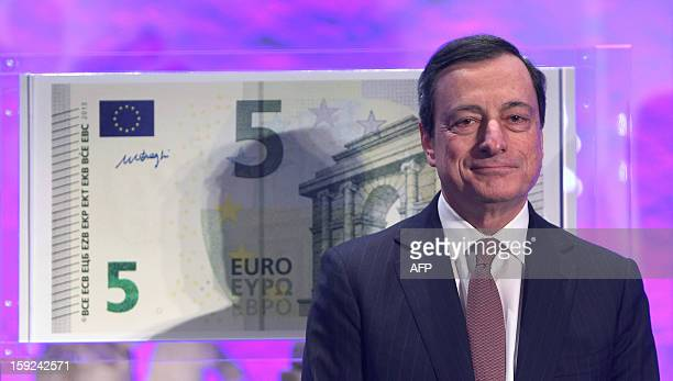 Mario Draghi President of the European Central Bank smiles in front of a giant five euro note during the unveiling ceremony of the new 5 euros...