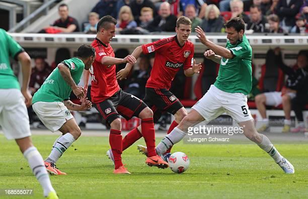 Mario Eggimann and Sergio Da Silva Pinto of Hannover tackle Lars Bender and Arkadiusz Milik of Leverkusen during the Bundesliga match between Bayer...