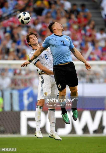 Mario Fernandes of Russia jumps for a header with Cristian Rodriguez of Uruguay during the 2018 FIFA World Cup Russia group A match between Uruguay...