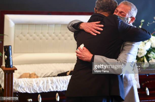 Mario Frausto embraces Dr. Michael C. Brown, minister, at the funeral for Frausto's husband Terrance Sheppard, who passed away due to COVID-19...