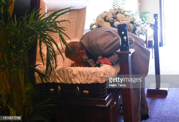 Mario Frausto kisses his deceased husband Terrance Sheppard, who passed away due to complications from COVID-19, amid an overflow of the deceased...