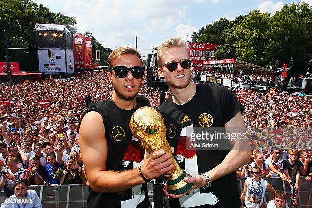 Mario Goetze and Andre Schuerrle celebrate on stage at the German team victory ceremony on July 15 2014 in Berlin Germany Germany won the 2014 FIFA...