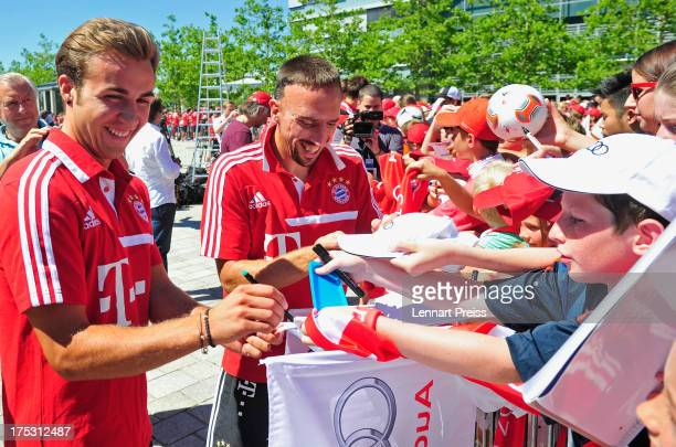 Mario Goetze and Frank Ribery of FC Bayern Muenchen give autographs to young fans during the handover of their new cars at Audi Forum on August 2...