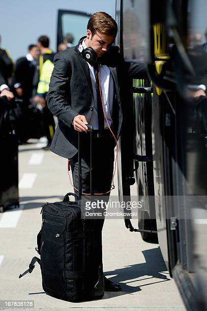 Mario Goetze heads towards the team bus during the Borussia Dortmund arrival at Dortmund Airport on May 1 2013 in Dortmund Germany