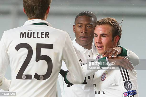 Mario Goetze of Bayern Muenchen celebrates scoring the 2nd team goal with his team mates David Alaba and Thomas Mueller during UEFA Champions League...
