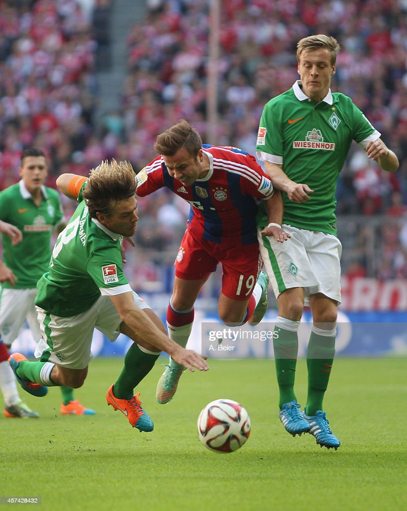 Mario Goetze (C) of Bayern Muenchen is tackled by Clemens Fritz (L) and Felix Kroos of Werder Bremen during the Bundesliga match between FC Bayern Muenchen and SV Werder Bremen at Allianz Arena on October 18, 2014 in Munich, Germany.
