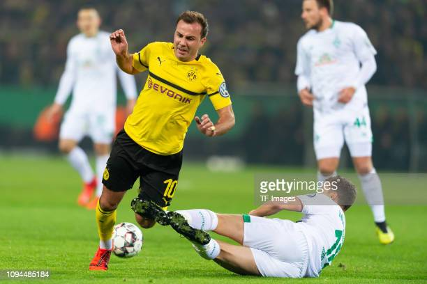 Mario Goetze of Borussia Dortmund and Niklas Moisander of SV Werder Bremen battle for the ball during the DFB Cup match between Borussia Dortmund and...
