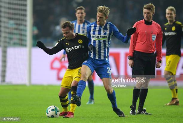 Mario Goetze of Borussia Dortmund Arne Maier of Hertha BSC and referee Christian Dingert during the game between Hertha BSC and Borussia Dortmund on...