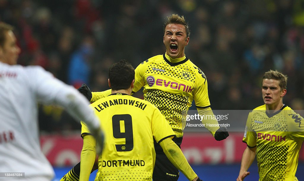 Mario Goetze (C) of Dortmund celebrates scoring the opening goal with his team mate Robert Lewandowski and bMarcel Schmelzer (R) whilst Manuel Neuer (L), keeper of Muenchen reacts during the Bundesliga match between FC Bayern Muenchen and Borussia Dortmund at Allianz Arena on November 19, 2011 in Munich, Germany.