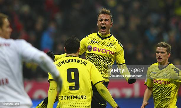 Mario Goetze of Dortmund celebrates scoring the opening goal with his team mate Robert Lewandowski and bMarcel Schmelzer whilst Manuel Neuer keeper...