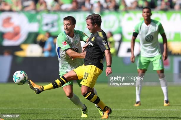 Mario Goetze of Dortmund competes with Ignacio Camacho of Wolfsburg during the Bundesliga match between VfL Wolfsburg and Borussia Dortmund at...