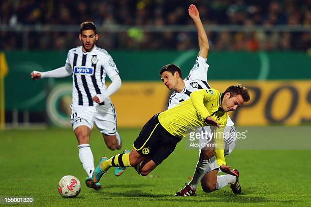 Mario Goetze of Dortmund is challenged by Andreas Hofmann of Aalen during the second round match of the DFB Cup between VfR Aalen and Borussia...