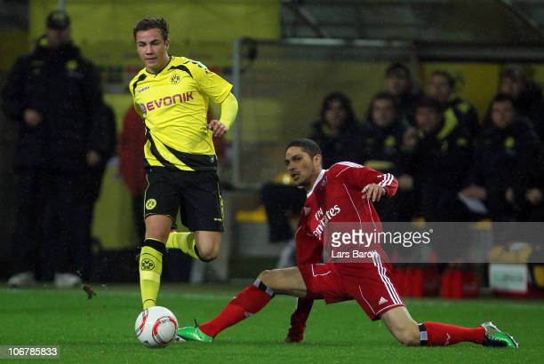 Mario Goetze of Dortmund is challenged by Paolo Guerrero of Hamburg during the Bundesliga match between Borussia Dortmund and Hamburger SV at Signal...