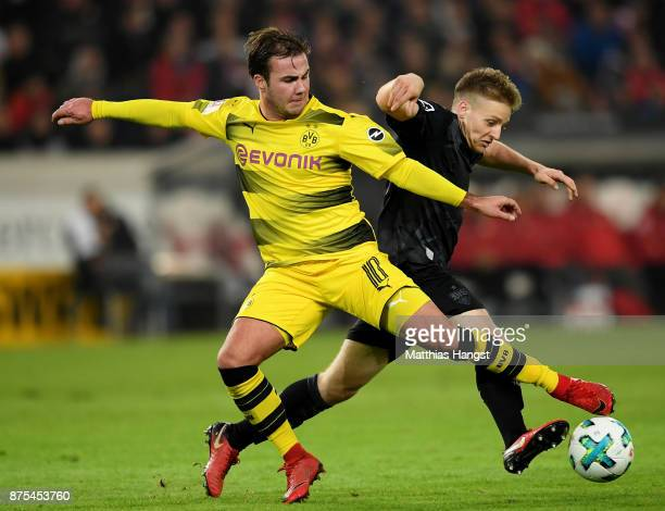 Mario Goetze of Dortmund is challenged by Santiago Ascacibar of Stuttgart during the Bundesliga match between VfB Stuttgart and Borussia Dortmund at...