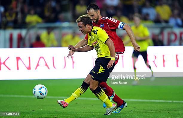 Mario Goetze of Dortmund scores his teams second goal next to Heiko Westermann of Hamburg during the Bundesliga match between Borussia Dortmund and...