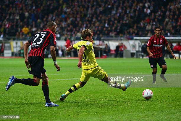 Mario Goetze of Dortmund scores his team's third goal against Bamba Anderson and Carlos Zambrano of Frankfurt during the Bundesliga match between...